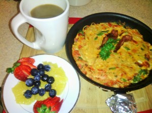 Cooked frittata with garnish of parsley/bacon strips with a serving of fresh fruits and coffee