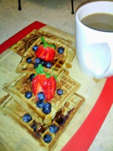 APPLE/BANANA WAFFLES ARE SERVED WITH FRESH BERRIES AS TOPPINGS ALONG WITH HOT COFFEE ON THE SIDE