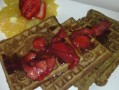 OATMEAL/FLAX SEED WAFFLES TOPPED BY SIMMERED STRAWBERRIES ALONG WITH ORANGE WEDGES/STRAWBERRY ON THE SIDE