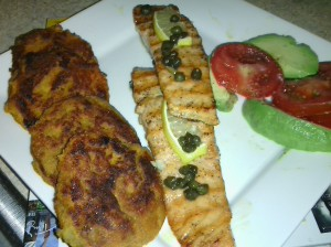 FINISHED DISH: GRILLED CITRUS/HONEY SALMON WITH A TOPPING OF CAPERS/LEMON, SWEET POTATO PATTIES AND SIDES OF AVOCADO AND TOMATO SLICES