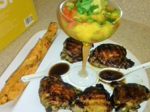 FINISH DISH OF GRILLED JERK CHICKEN THIGHS, MANGO SALSA AND SWEET POTATO WEDGES